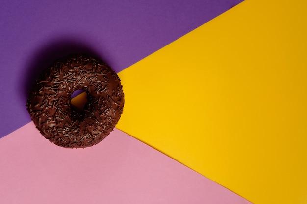 분홍색과 노란색 배경에 초콜릿 도넛