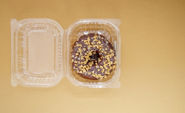 Chocolate donut in a plastic container on a brown or coffee background. takeaway breakfast concept. one donut is packed in a plastic box for delivery. sweet pastries delivered to your home. top view.