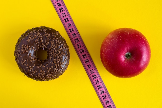 Chocolate donut,red apple and pink centimeter on yellow