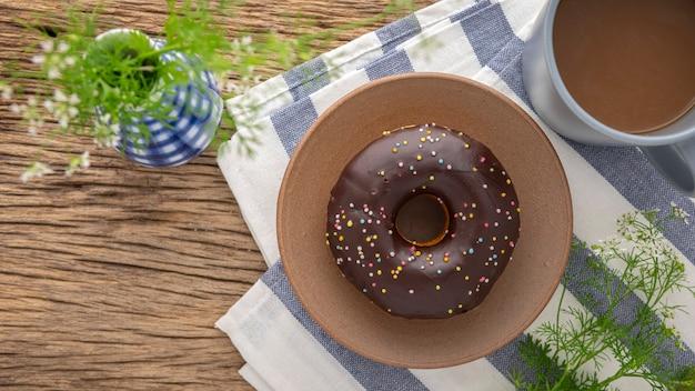 Шоколадный пончик с посыпкой на керамической тарелке рядом с кофе и вазой на салфетке и деревенском фоне текстуры натурального дерева, легкая еда во время перерыва, вид сверху