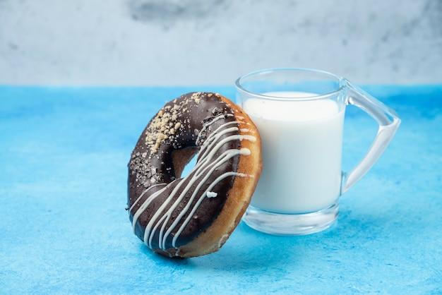 Шоколадный пончик со стаканом молока на синем столе.