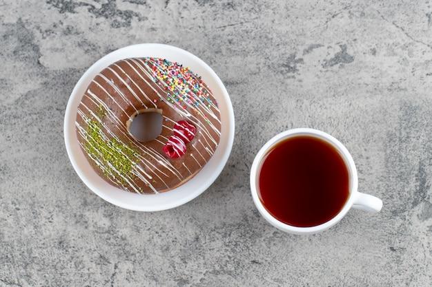 石の背景にベリーとスプリンクルと熱いお茶のカップとチョコレートドーナツ。