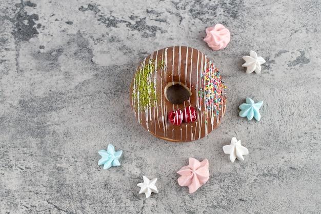 Шоколадный пончик с красочными конфетами безе на каменном фоне.