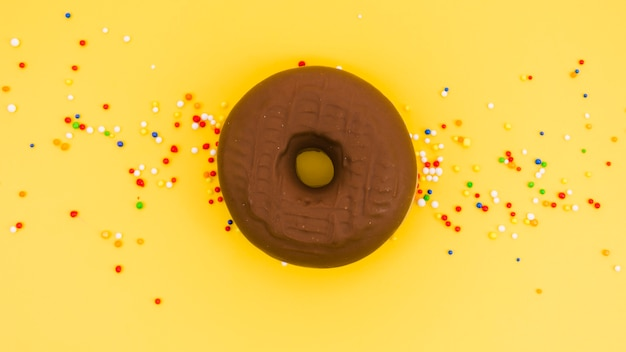 Chocolate donut with colorful sprinkles on yellow background