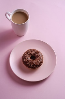 Chocolate donut with sprinkles on plate near to cup of coffee, sweet glazed dessert food and hot drink on pink minimal table, angle view
