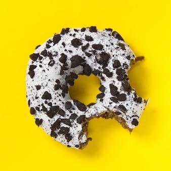 노란색 테이블에 흰색 유약 초콜릿 도넛