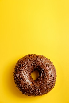 Chocolate donut on yellow wall top view