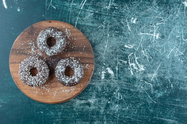 Chocolate donuts on the board , on the blue background. high quality photo
