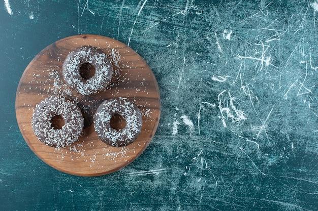 파란색 배경에 보드에 초콜릿 도넛. 고품질 사진