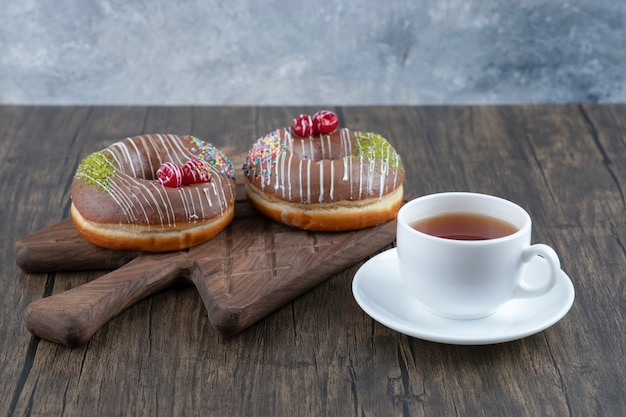 홍차 한잔과 함께 나무 보드에 초콜릿 도넛.