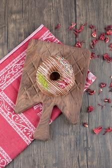 Шоколадные пончики на деревянной доске с высушенными лепестками роз.
