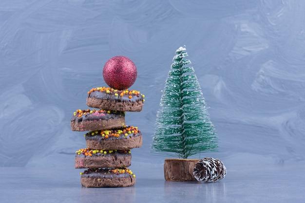クリスマスボールとクリスマスの小さな木とチョコレートドーナツ