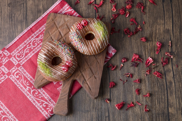 Chocolate donuts on wooden board with dried rose petals.