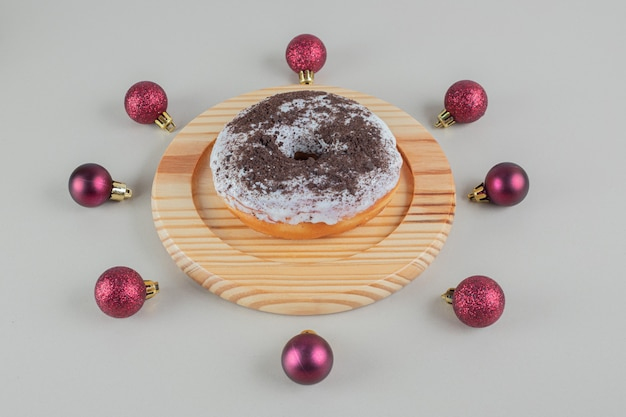 Chocolate doughnut with christmas balls .
