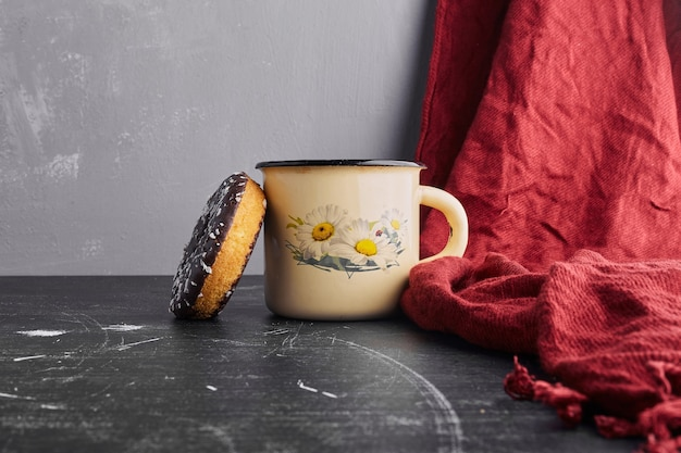 Chocolate doughnut with a cup of tea.