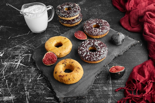 Chocolate doughnuts and buns on a stone board.
