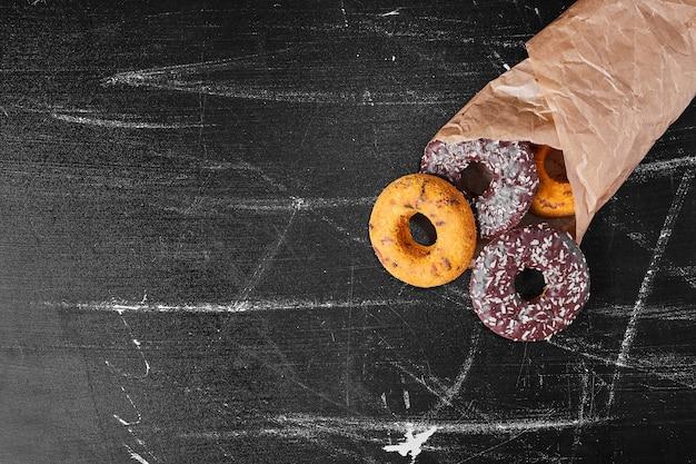 Шоколадные пончики в бумажной упаковке.