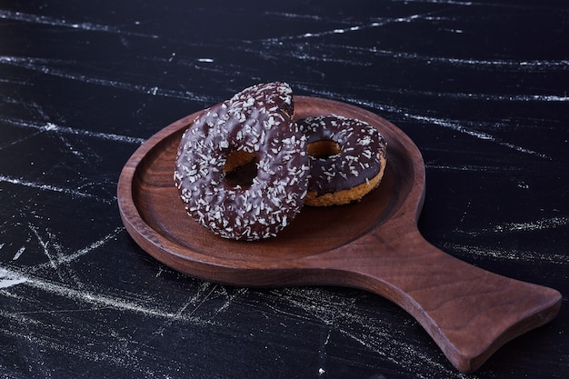 Chocolate doughnuts isolated on black surface in a wooden platter.