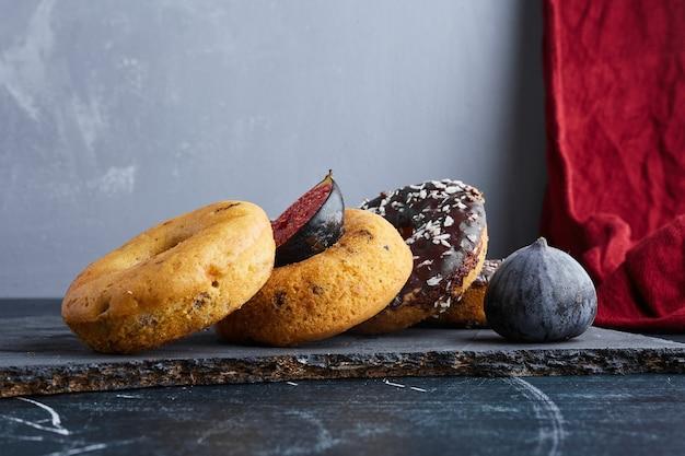 Шоколадные пончики на черном каменном блюде.