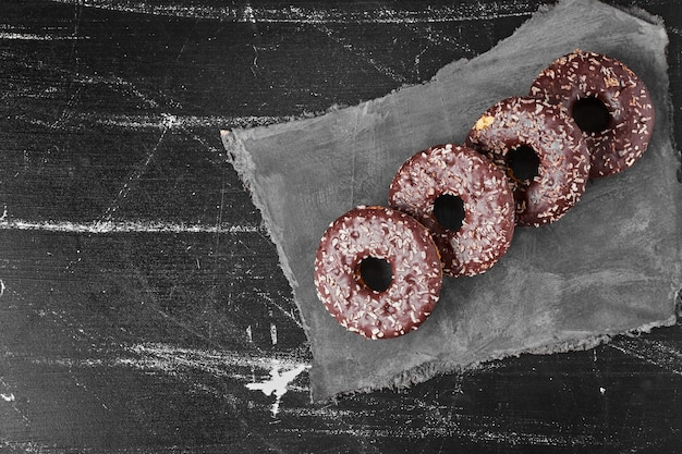Chocolate doughnuts on a stone platter . high quality photo