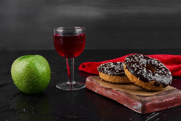 Chocolate doughnuts on a wooden board with apple and wine.