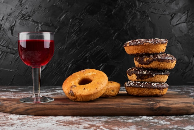 Chocolate doughnuts on a wooden board with a glass of wine.