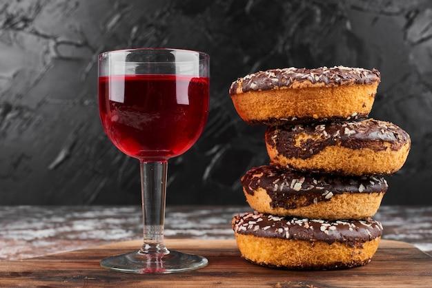 Ciambelle al cioccolato su una tavola di legno con vino.