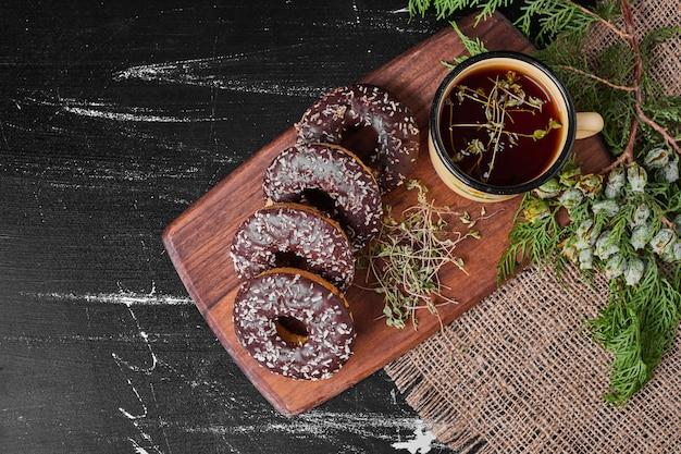 Ciambelle al cioccolato su un piatto di legno con tè.