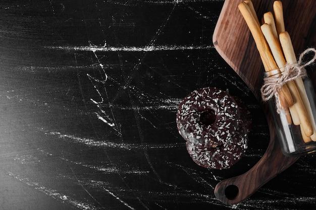 Ciambelle al cioccolato su un piatto di legno con bastoncini di cialda intorno.