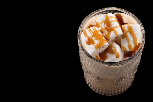 Chocolate drink   marshmallow and caramel sauce on black surface.