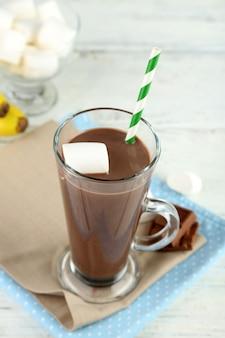 머그에 마시멜로를 넣은 초콜릿 음료, 나무 배경