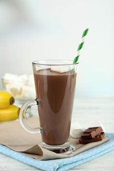 Шоколадный напиток с зефиром в кружке на деревянной поверхности