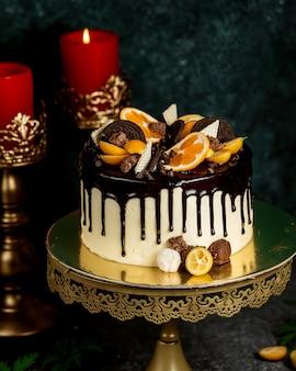 Torta gocciolante al cioccolato guarnita con biscotti e cialde al cioccolato all'arancia