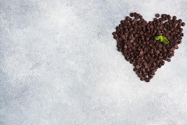灰色のコンクリートの上にハートの形に配置されたチョコレートの滴。デザートデコレーション用チョコレートピース。