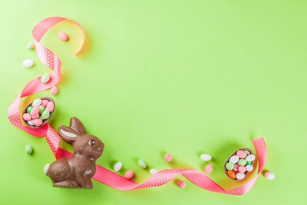 Chocolate easter bunny, candy eggs, quail eggs and festive ribbon