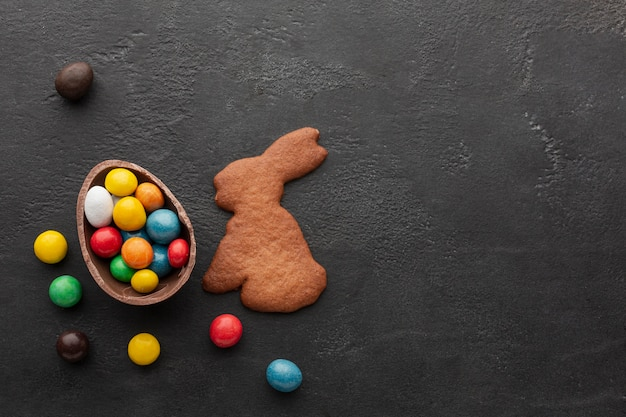 Chocolate easter egg filled with colorful candy and bunny shaped cookie