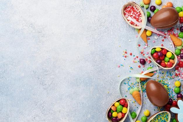 Шоколадные пасхальные яйца и красочные сладости на сером взгляде столешницы. плоская планировка с местом для ваших поздравлений
