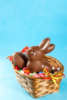 Chocolate easter eggs, bunny and sweets in the basket on light blue surface, easter concept
