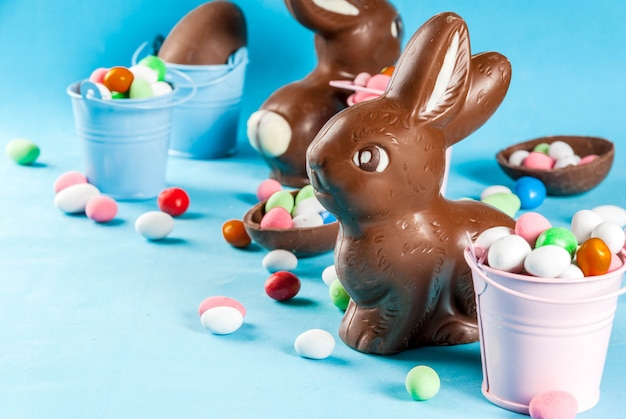 Chocolate easter eggs, bunny and sweets on light blue , easter ,