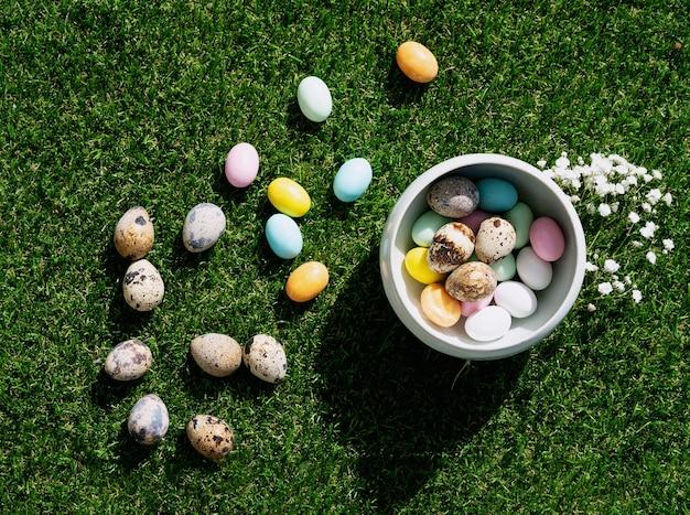 パステルカラーで釉薬をかけたチョコレートのイースターエッグとウズラの卵をボウルに入れ、緑の芝生の上に置きます。ハッピーイースターのコンセプト。スペースをコピーします。上面図