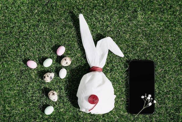 パステルカラーで釉薬をかけたチョコレートのイースターエッグと緑の草の上にウズラの卵。バニー型の白いベーキングペーパー。黒の携帯電話。ハッピーイースターのコンセプト。スペースをコピーします。上面図 Premium写真