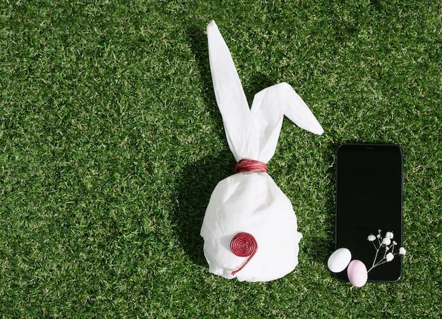 パステルカラーで釉薬をかけたチョコレートのイースターエッグと緑の草の上にウズラの卵。バニー型の白いベーキングペーパー。黒の携帯電話。ハッピーイースターのコンセプト。スペースをコピーします。上面図