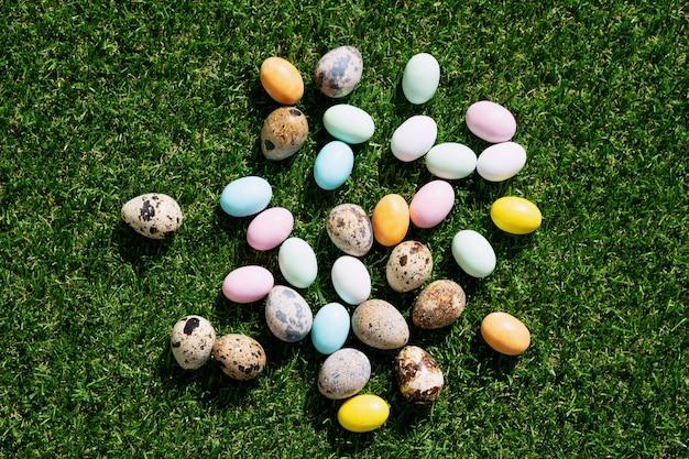 パステルカラーで釉薬をかけたチョコレートのイースターエッグと緑の草の上にウズラの卵。ハッピーイースターのコンセプト。スペースをコピーします。上面図