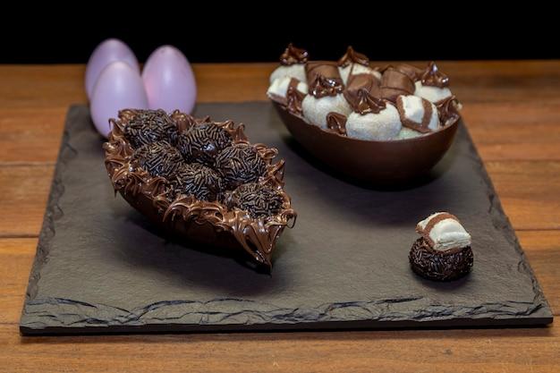Шоколадные пасхальные яйца на черном камне с деревянным фоном