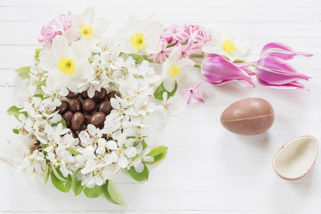 Chocolate easter eggs with spring flowers on wooden background
