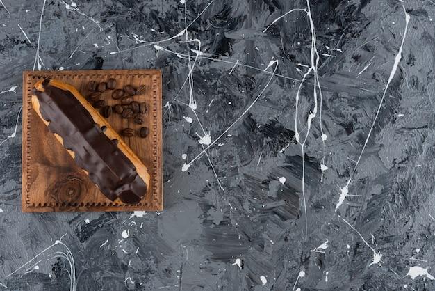 大理石のテーブルに置かれたコーヒー豆とチョコレートエクレア。