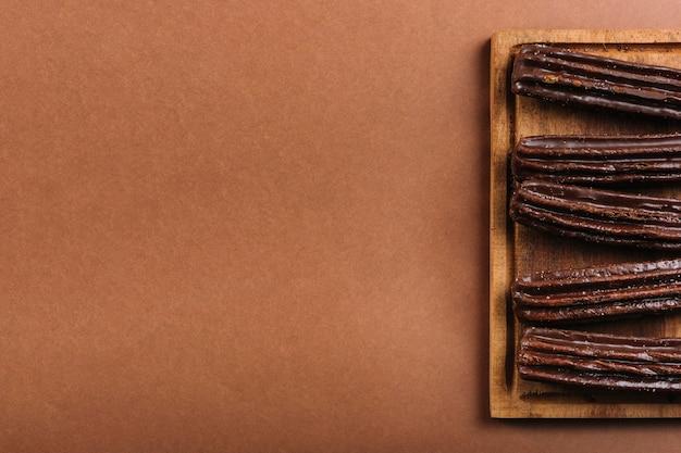 Chocolate eclairs on chopping board