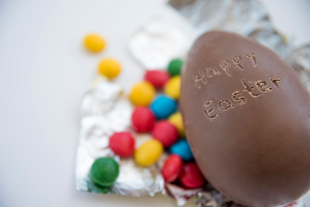 Chocolate egg with happy easter title and candies on foil