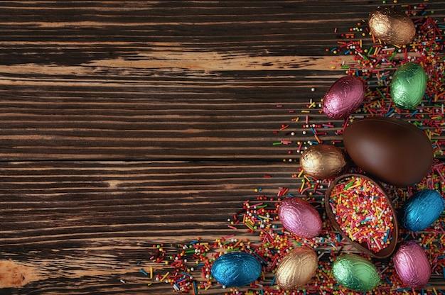 暗い木製のテーブルの上のホイルのチョコレートの卵