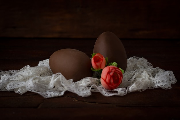 Chocolate eggs, white lace tape, artificial decorative roses on dark wooden surface. easter concept